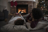 Young couple in pajamas laying, relaxing by fire near Christmas tree in living room - HEROF16345