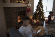 Young man in pajamas relaxing, using digital tablet near fire and Christmas tree in living room - HEROF16348