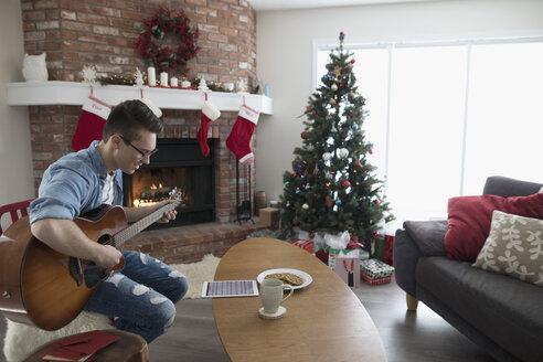 Young man with digital tablet playing guitar in Christmas living room - HEROF16351
