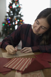 Teenage girl writing letter to Santa in Christmas living room - HEROF16357