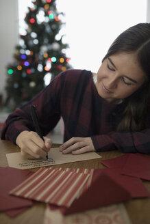 Teenage girl writing letter to Santa in Christmas living room - HEROF16357