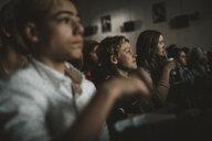 Tweens watching movie, eating popcorn and drinking soda in dark movie theater - HEROF16387