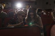 Tweens in 3d glasses watching movie, texting with smart phone in dark movie theater - HEROF16390