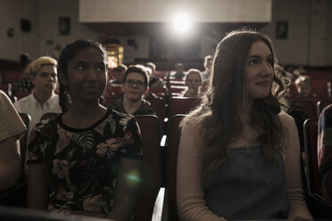 Tween girl friends watching movie in dark movie theater - HEROF16393