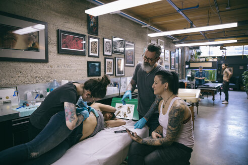 Tattoo artists and client tattooing side of client in tattoo studio - HEROF16417