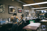 Tattoo artist tattooing side of client in tattoo studio - HEROF16432