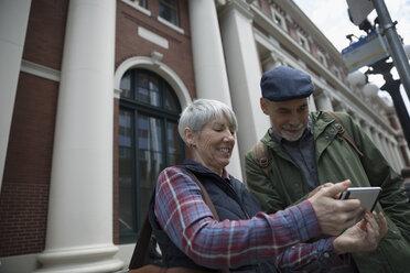 Smiling senior couple using smart phone on urban sidewalk - HEROF16453