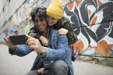 Smiling young couple with camera phone taking selfie along urban graffiti wall - HEROF16459