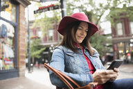 Smiling mature woman in hat texting with smart phone on urban sidewalk - HEROF16462