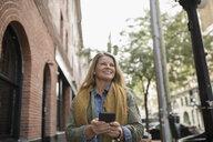 Smiling mature woman texting with smart phone on urban sidewalk - HEROF16465