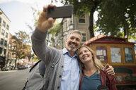 Smiling mature couple with camera phone taking selfie on urban street - HEROF16474