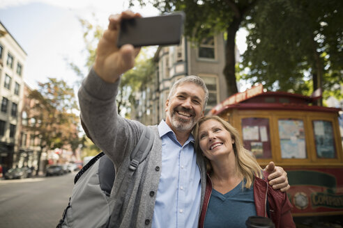 Smiling mature couple with camera phone taking selfie on urban street - HEROF16474