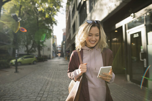 Smiling blonde young woman texting with smart phone on sunny urban sidewalk - HEROF16480