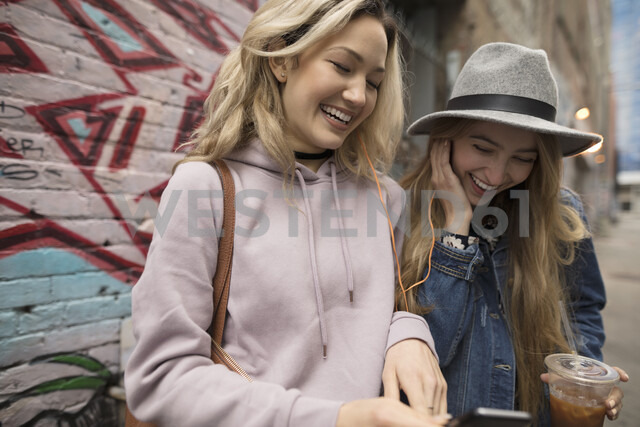 Smiling young women friends drinking iced coffee and texting with smart phone - HEROF16483
