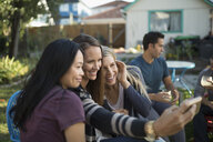 Smiling women taking selfie with smart phone at backyard barbecue - HEROF16486