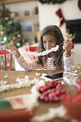 Smiling girl stringing popcorn Christmas decoration at table - HEROF16495