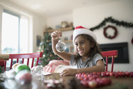 Smiling girl in Santa hat holding tiny terrarium ornament at table with Christmas decorations - HEROF16501