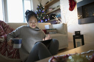Smiling woman drinking coffee and using digital tablet in Christmas living room - HEROF16510