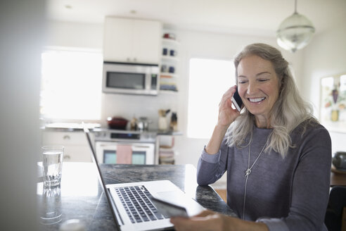 Smiling senior woman with credit card paying bills, talking on cell phone at laptop in kitchen - HEROF16513
