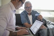Son helping senior father with credit card paying bills online - HEROF16558