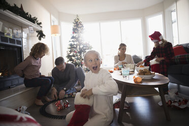 Surprised girl in pajamas opening Christmas stocking with family in living room - HEROF16576