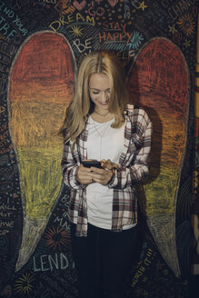 Smiling Caucasian tween blonde girl texting with smart phone against wall with chalk wings - HEROF16582