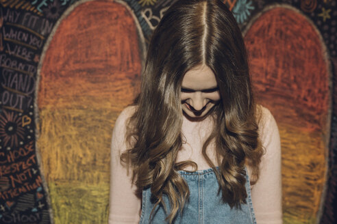 Smiling, shy Caucasian brunette tween girl against wall with chalk wings - HEROF16585