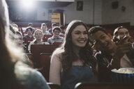 Smiling tween couple watching movie, talking in dark movie theater - HEROF16600