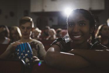 Smiling Indian tween girl watching movie in dark movie theater - HEROF16603