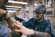 Tattoo artist preparing forearm of client in tattoo studio - HEROF16621