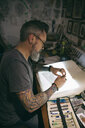 Tattoo artist sketching at light table in tattoo studio office - HEROF16630