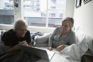 Smiling senior couple in pajamas relaxing, using laptop on bed in urban apartment - HEROF16639