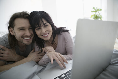 Smiling, happy couple video chatting with laptop on bed - HEROF16645