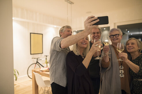 Smiling, happy senior friends drinking white wine and taking selfie with camera phone, enjoying social gathering - HEROF16651
