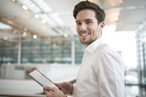 Portrait of happy young businessman with tablet - PNEF01238