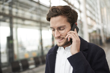 Smiling young businessman wearing glasses talking on cell phone - PNEF01244