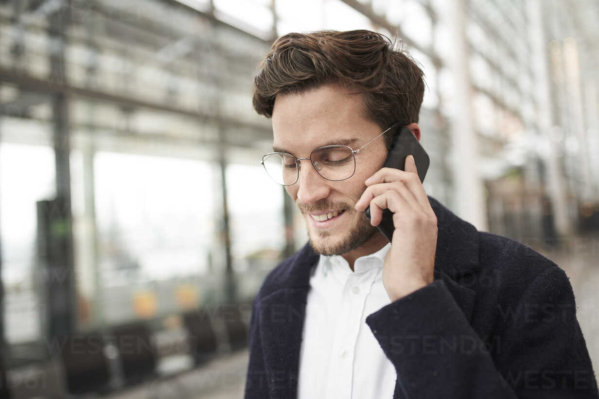 Smiling young businessman wearing glasses talking on cell phone - PNEF01244 - Philipp Nemenz/Westend61