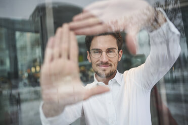 Portrait of young businessman behind glass pane shaping a hand frame - PNEF01247
