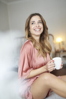 Smiling young woman in dressing gown sitting on bed with cup of coffee - PNEF01256