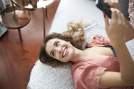 Happy young woman in dressing gown lying in bed holding cell phone - PNEF01265