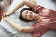 Laughing young woman in dressing gown lying in bed - PNEF01271