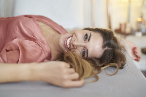 Portrait of happy young woman in dressing gown lying in bed - PNEF01274