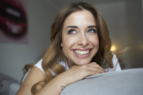 Portrait of happy young woman on couch - PNEF01286