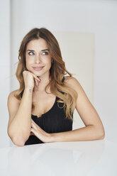 Smiling young woman wearing black dress looking sideways - PNEF01289