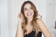 Happy young woman wearing black dress looking sideways - PNEF01292