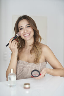 Portrait of smiling young woman applying make-up - PNEF01295