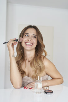 Laughing young woman applying make-up - PNEF01298