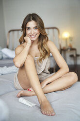 Portrait of smiling young woman sitting on bed - PNEF01304