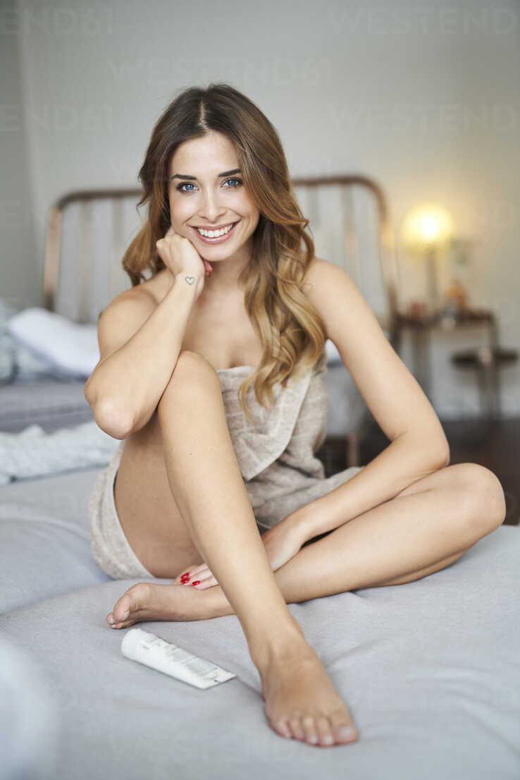 Portrait of smiling young woman sitting on bed - PNEF01304 - Philipp Nemenz/Westend61