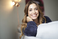 Portrait of happy young woman on couch - PNEF01307